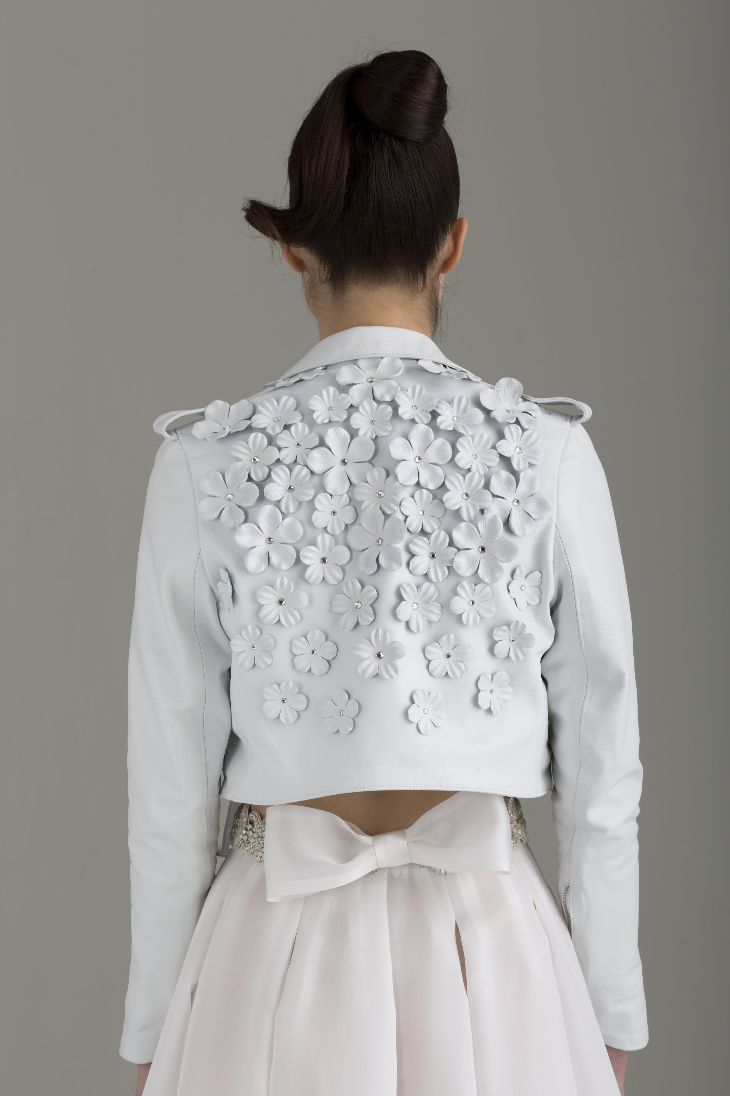 "NKB17-84001    ""Nathalie"" Cropped Lambskin Leather MC Jacket Embellished w/ Hand-Made Leather Flowers & Swarovski Crystals;  NKB17-81002  ""Apoidea"" Satin and Mesh Crop Top&  NKB17-83006  ""Magnolia"" White Silk Gazar Multi Layers Pleat Skirt"