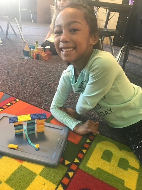A student from Grassy Creek Elementary School shows off a LEGO design from her classroom project.
