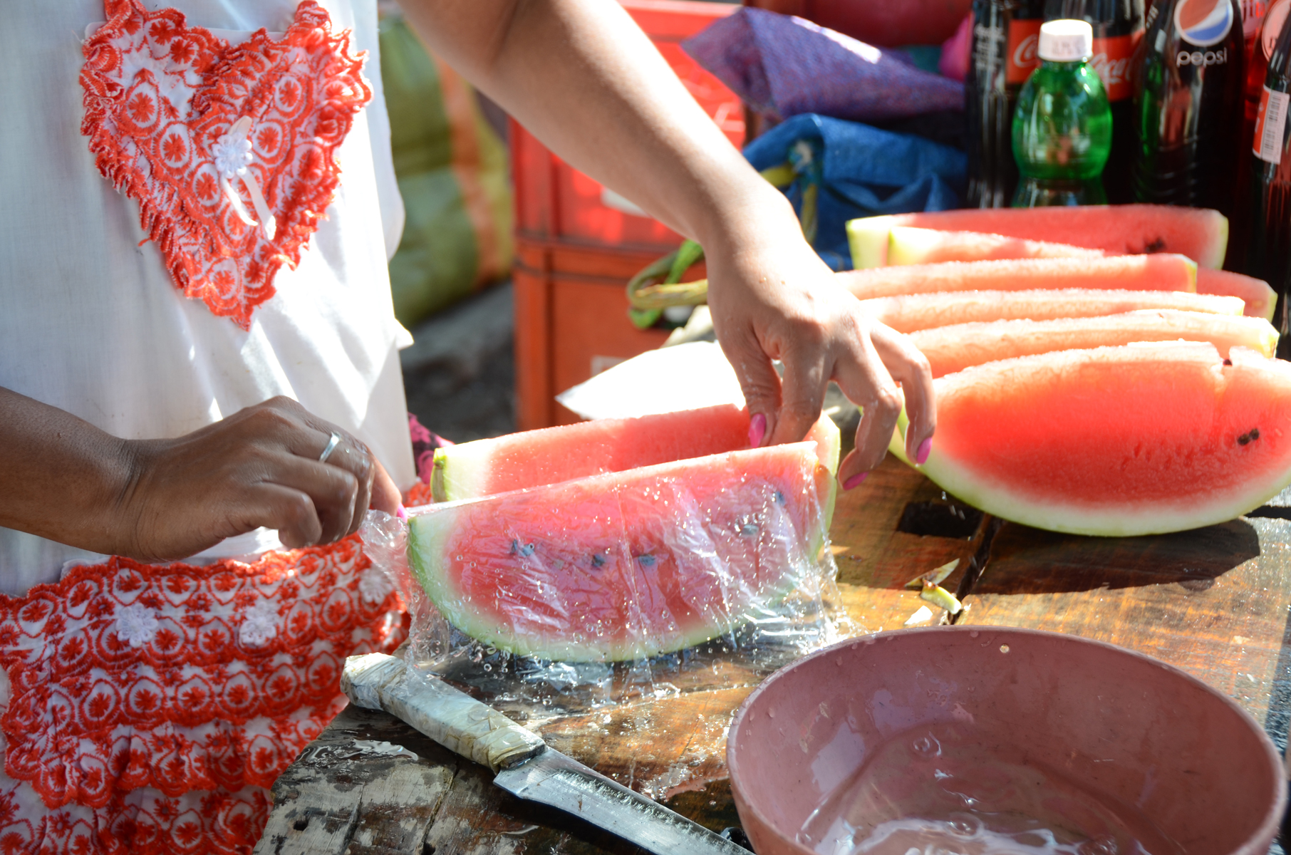 Dayani wrapping watermelon slices at her stand in the Mercado Oriental (2012). Photo by Elizabeth Kay.