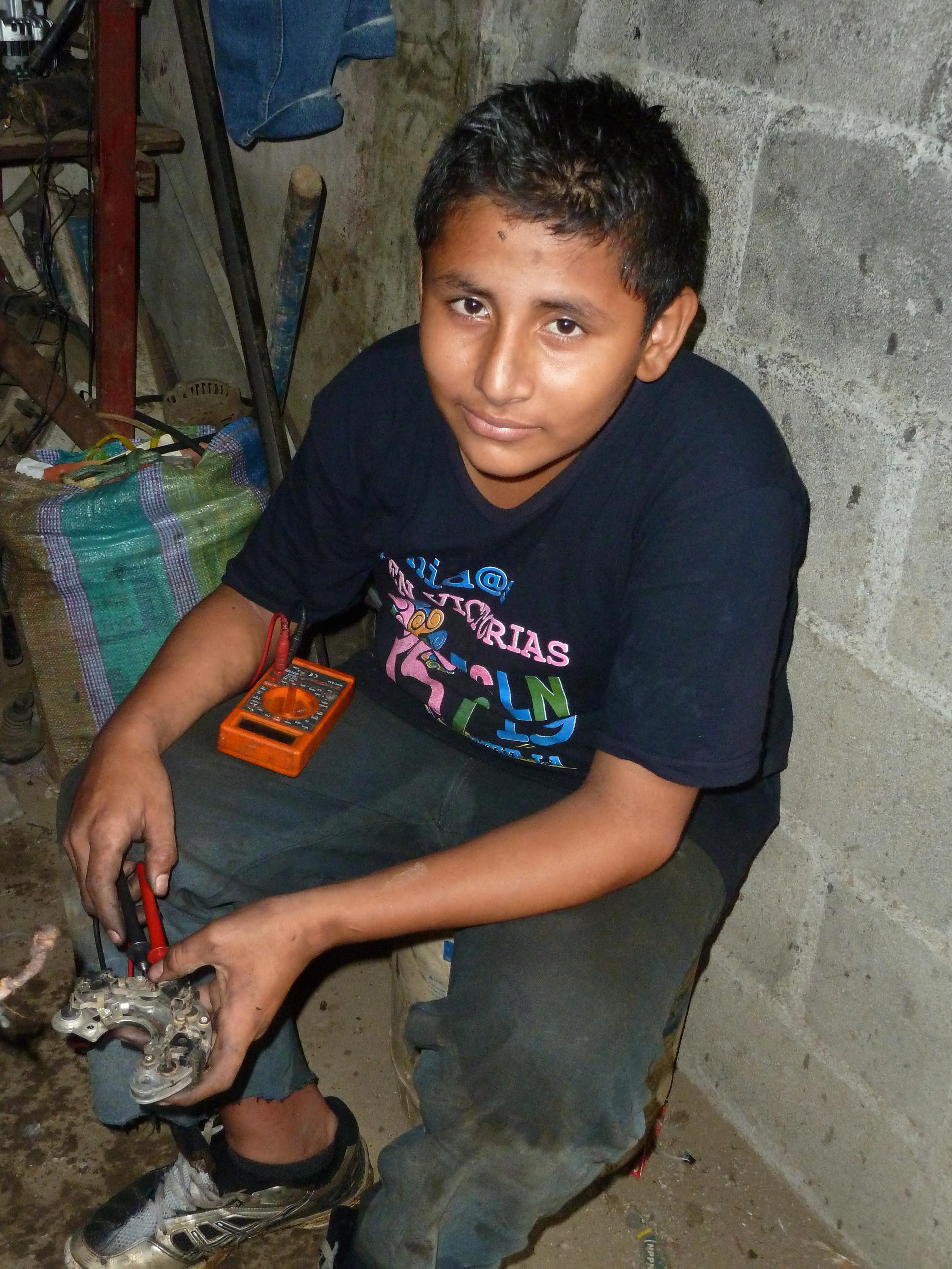 El hijo de Dayani, Gabriel, aprende electrónica automotriz en un taller de Managua (2014). Foto de Douglas Haynes.