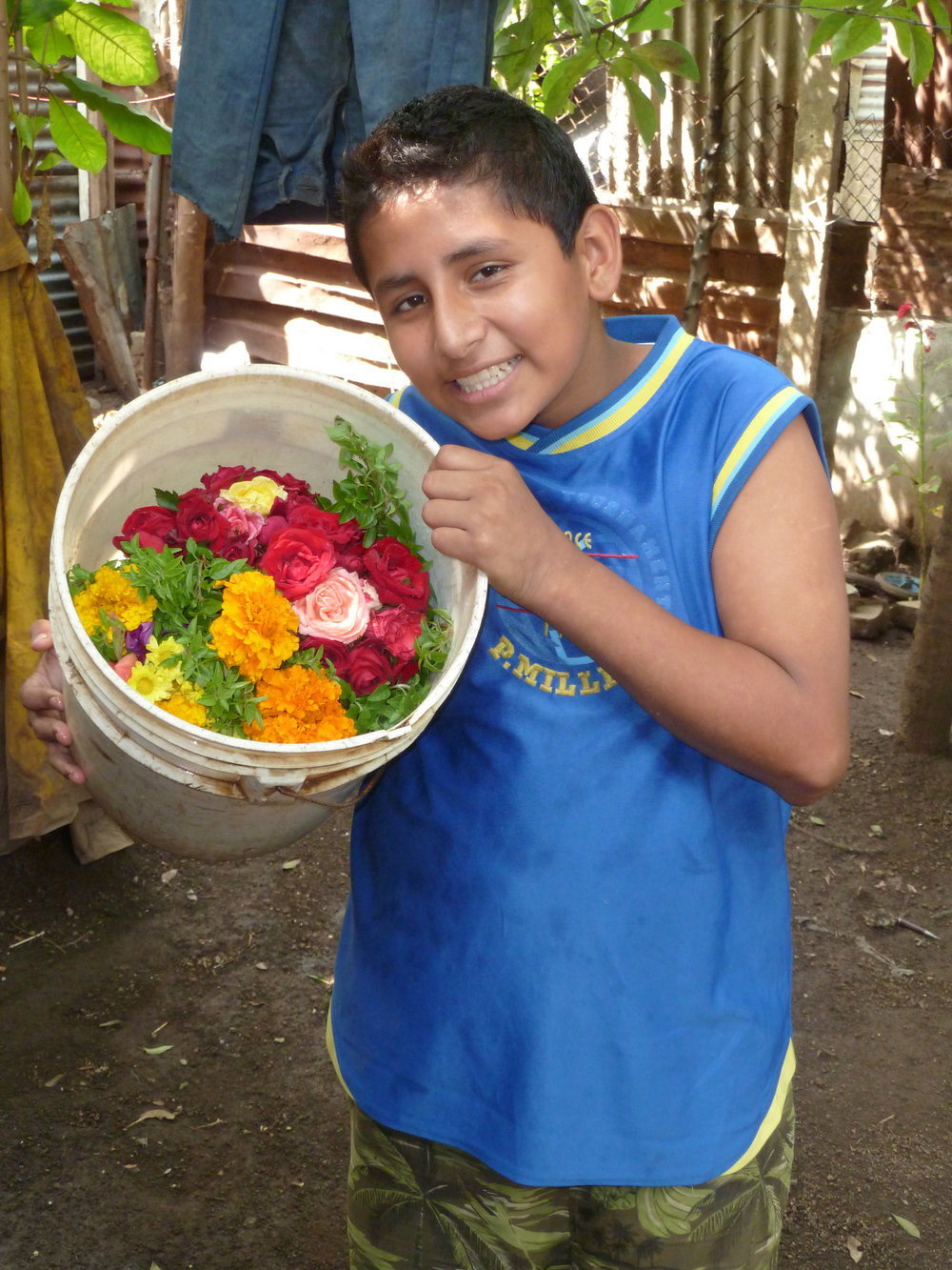 Gabriel con un balde de flores para la tumba de su hermano Yader (2014). Foto de Douglas Haynes.