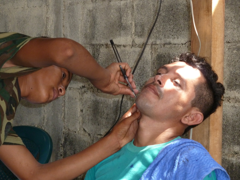 Edwin en su clase de peluquería, afeitando a su padre Noel (2014). Foto de Douglas Haynes.