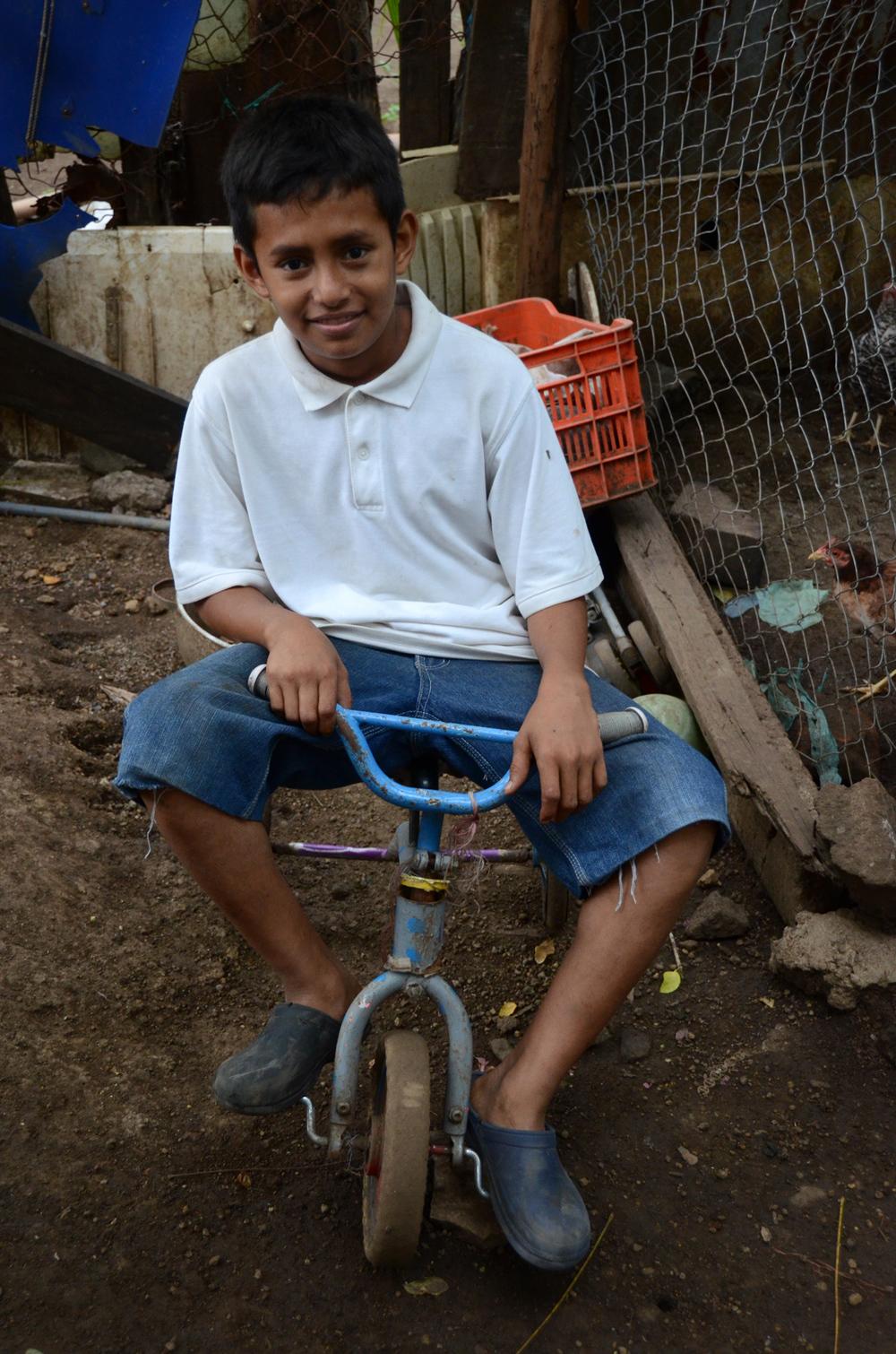 Edwin Edwin montando el triciclo de su difunto hermano Yader afuera de su casa en Managua. (2012). Foto de Elizabeth Kay.
