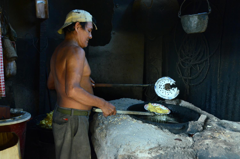 El padre de Dayani, César, fríe platanitos en su casa del Mercado Oriental (2012). Foto de Elizabeth Kay.