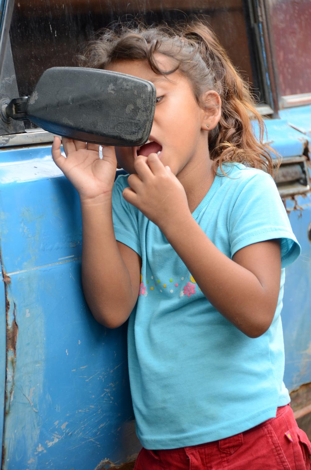 La sobrina de Yadira, Tamara, se revisa un diente flojo en el espejo retrovisor (2012). Foto de Elizabeth Kay.