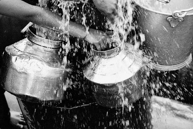 """Photo: Ross Pollackvia  flickr commons         Mumbai:Maharashtran'sfilling up their water cans off a """"borrowed"""" pressure valve on a main city water pipe. A daily ritual for the entire family to be able to access increasingly scarce water."""
