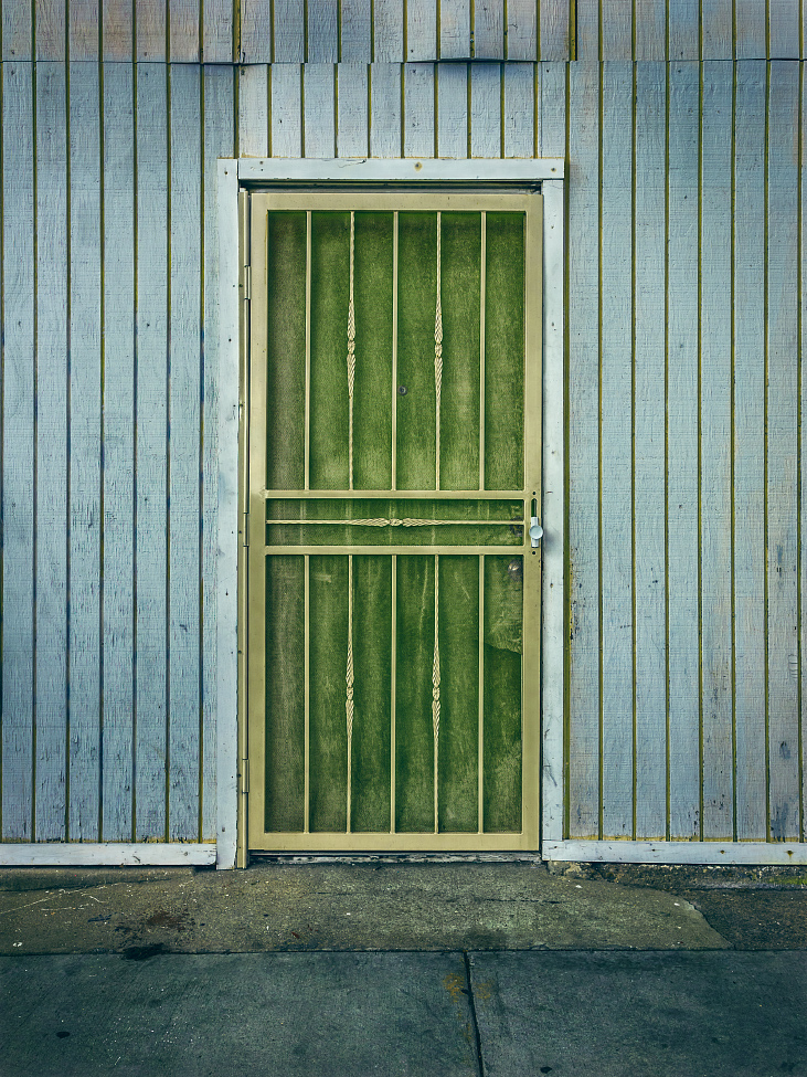 |#8|  Moss Green   A sickly gate encloses the dusty frame. The warped and buckled siding puckers away from the surface. Mismatched paint in the grout lines suggests a quick and dirty cover-up.