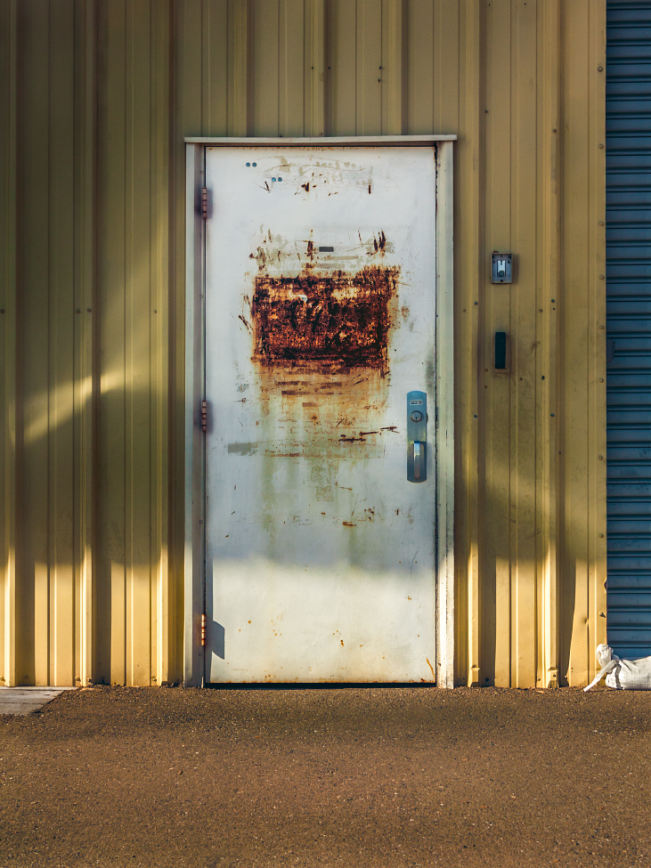 |#17|  Timberwolf   Corrugated aluminum siding emblazoned with refracted light resembling a poorly focused magnifying glass. The hot asphalt bears few witnesses to the many who have stood before it, defacing the now squarely rusted front.