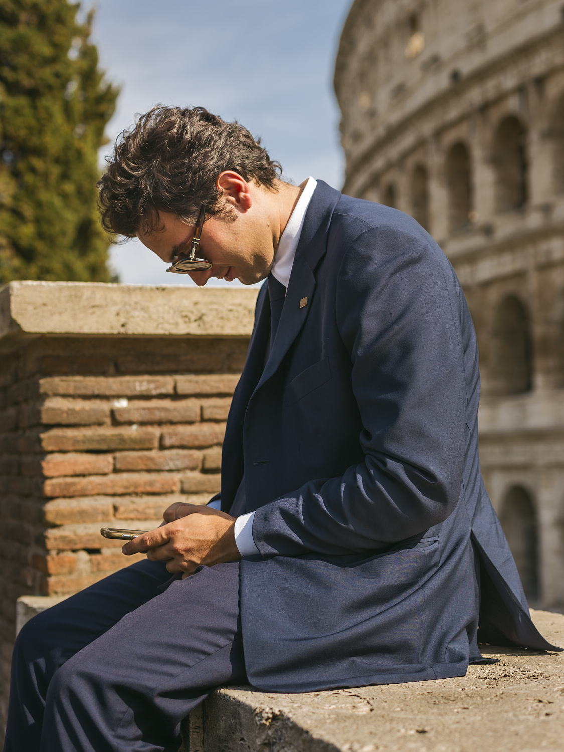 Businessman texting outside the Colosseum.