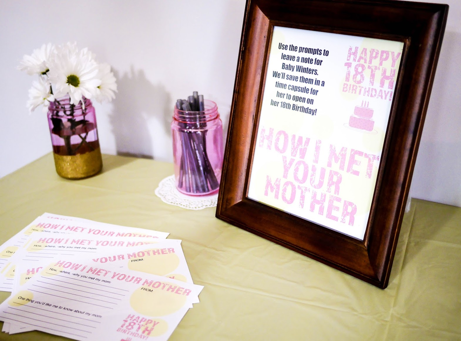 A frame for our free printable sign and cute jars to hold pens makes for an adorable station for guests to leave a fun message for baby's 18th birthday.