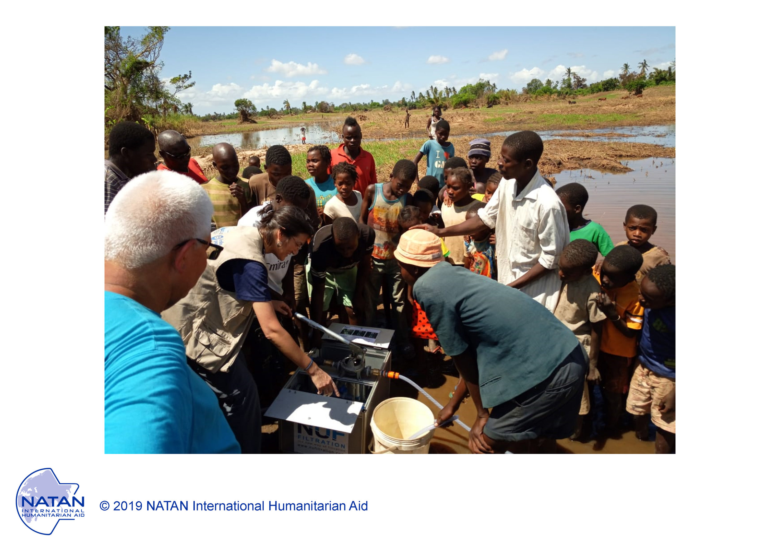 Mozambique 2019 - following cyclone idai, NATAN team teaching local villagers to use portable water filter near a source of contaminated water