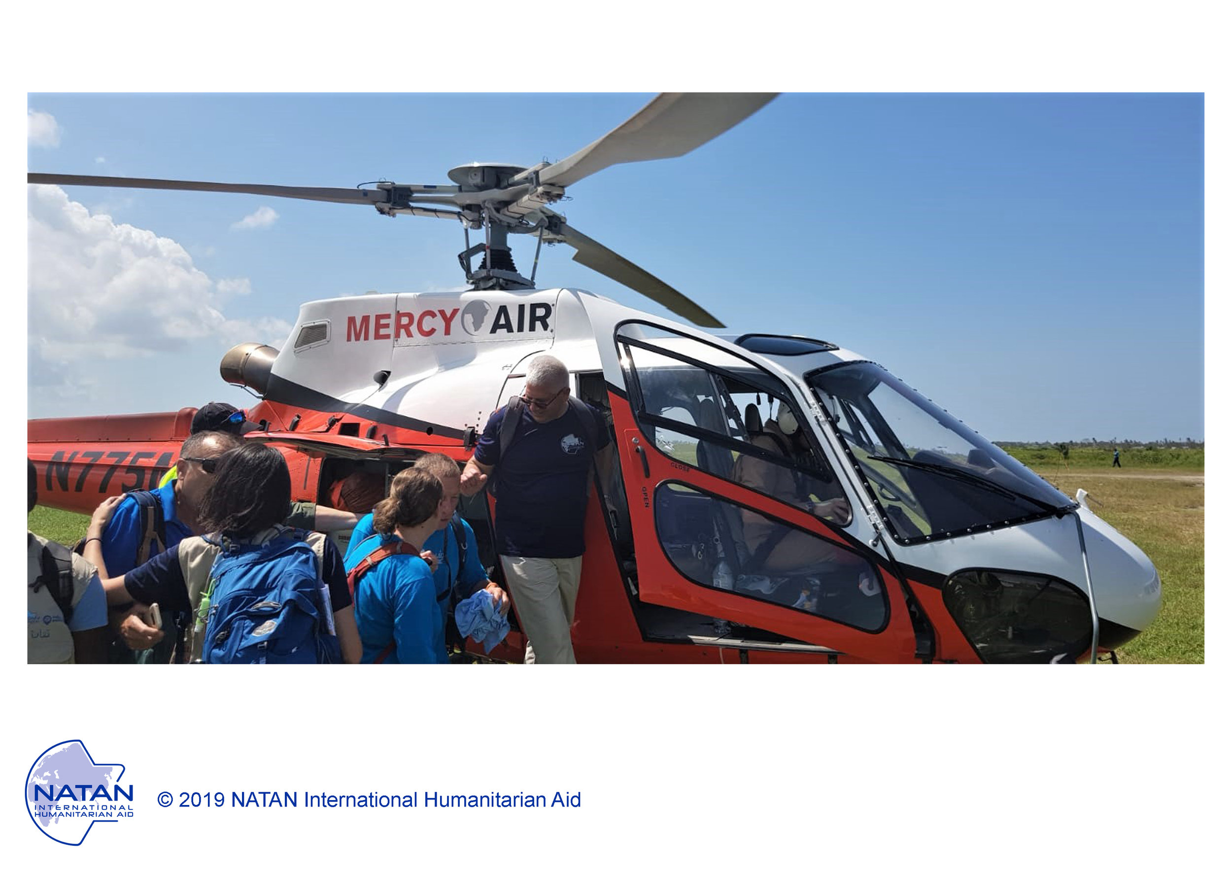 mozambique 2019 - natan team bording helicopter flown by partner, mercy air, to set up field clinics in remote locatinos follwoing cyclone idai