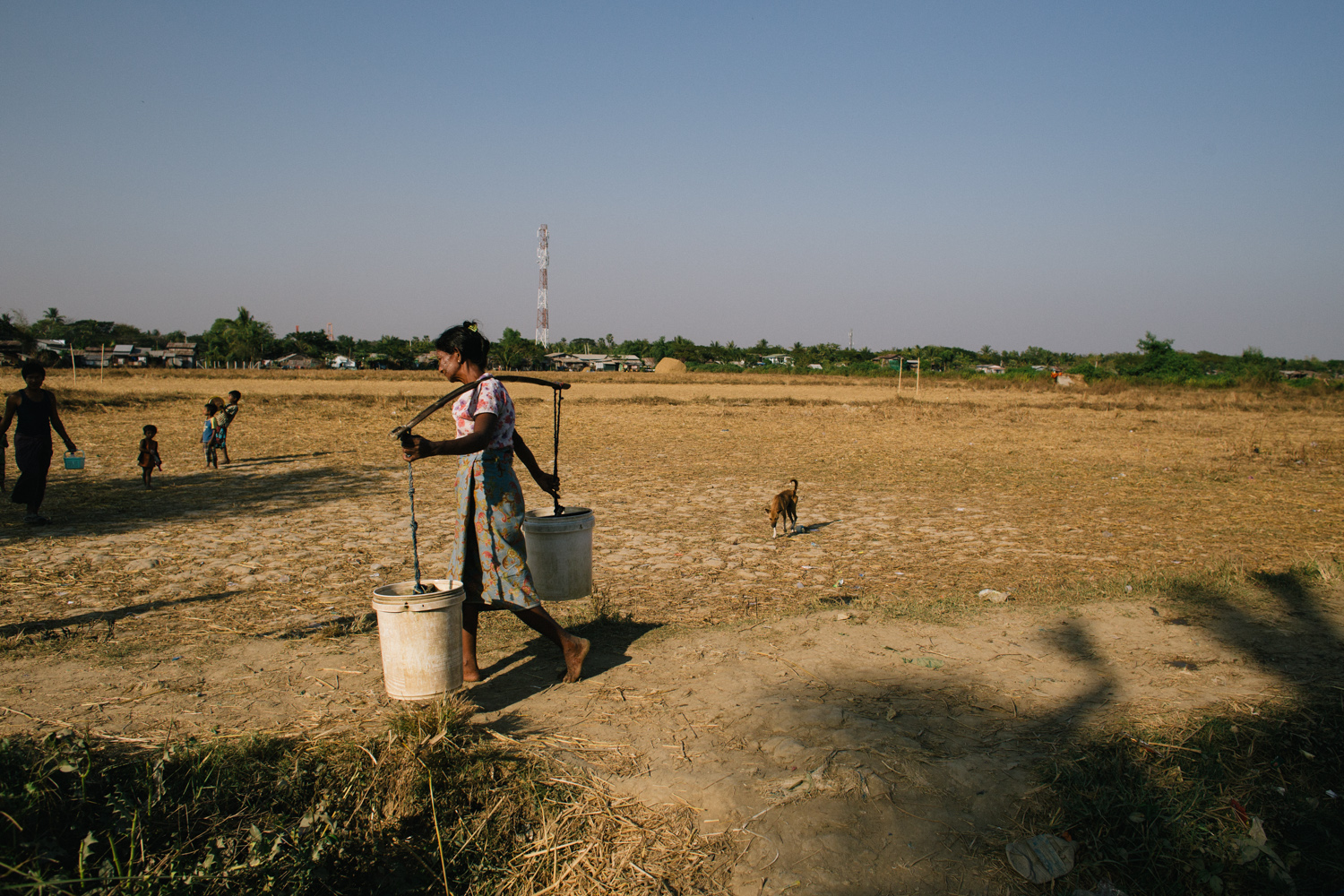 A woman carry two heavy buckets of water on the shoulder ,