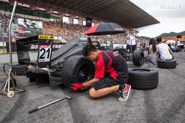 技工在後面換輪胎,遊人在前面拍照