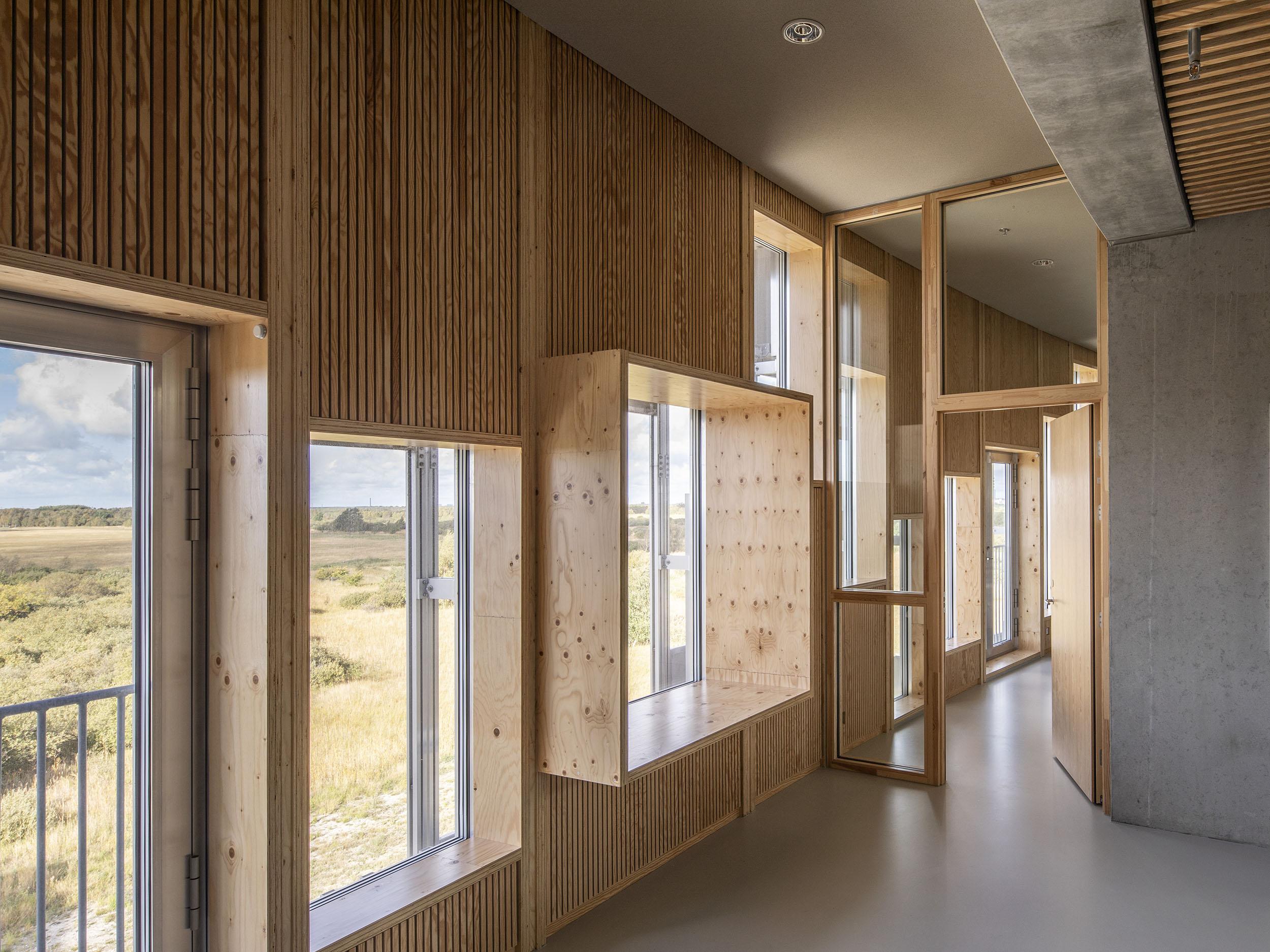 Indvendigt er facaden foret med finér i fyrretræ, der former sig til vinduesnicher og reoler, skaber små rum i det store rum, dæmper akustikken og giver plads til rolige pauser i en skoledag fuld af bevægelse.