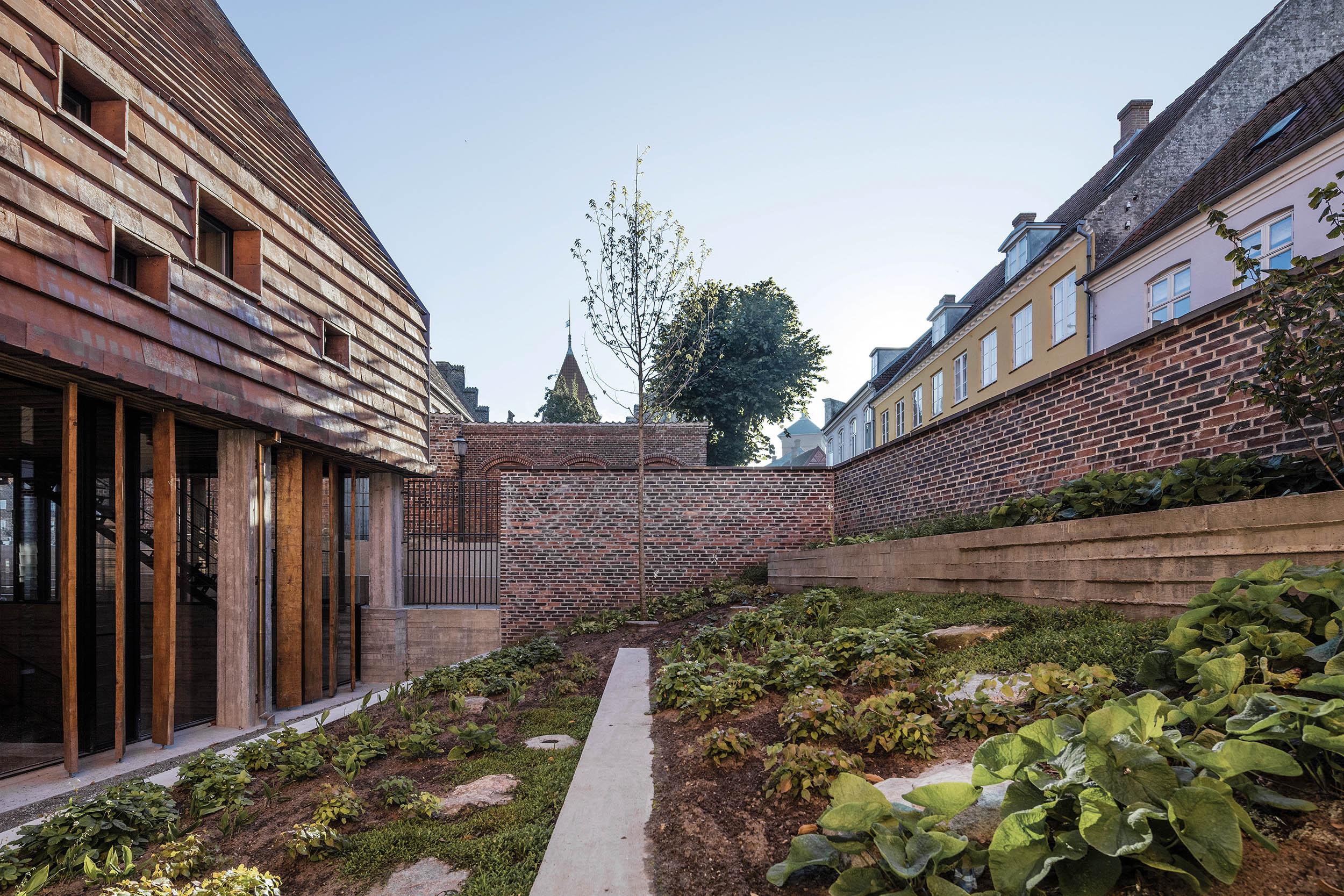 Mod syd er der anlagt en intim gårdhave, afgrænset af en mur langs Sønderportsgade og Rykind.