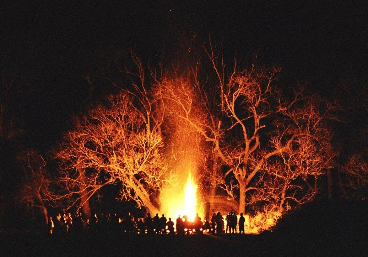 Men gathered at a huge fire