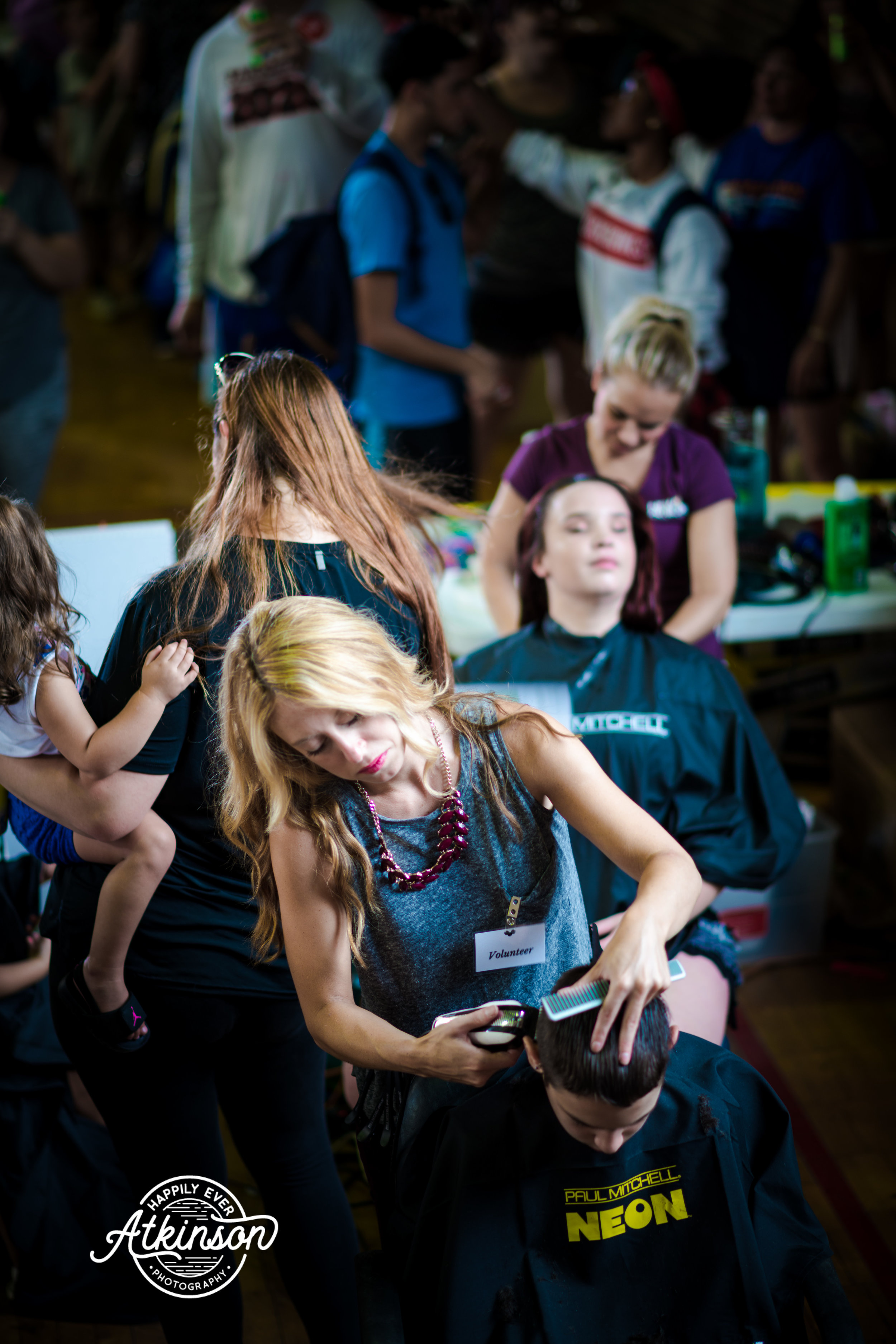 Woman cuts hair in front of a crowd