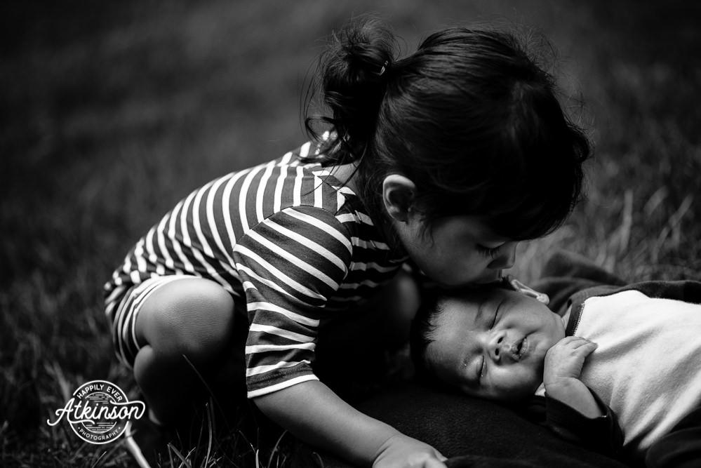 big sister kisses newborn brother