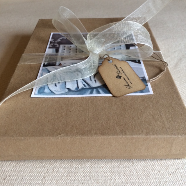 Gift box of 8 fold note cards on kraft paper, wrapped with a fancy ribbon and coffee-stained tag.