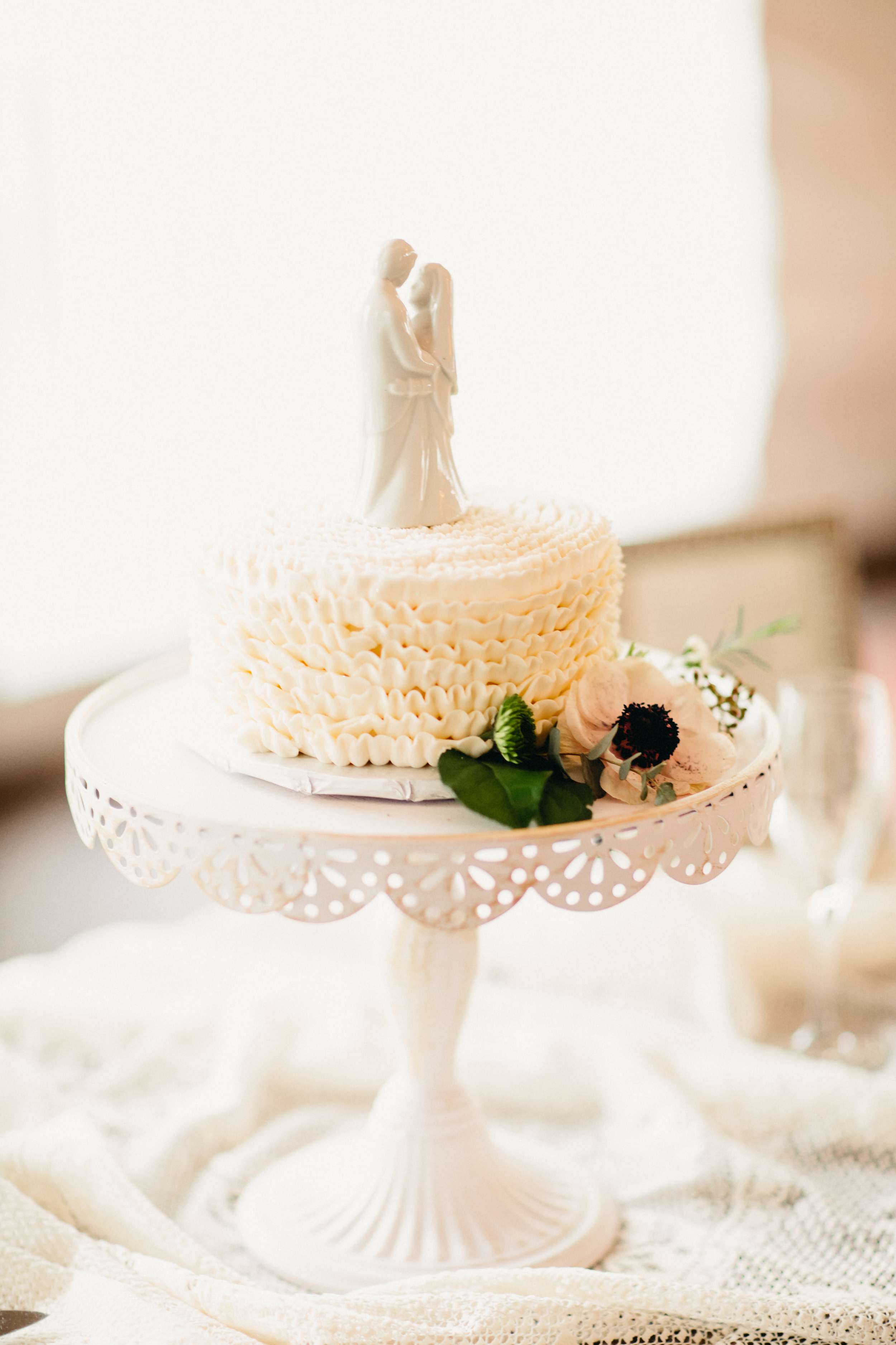 A wedding cake doesn't need to be sky-high! A single-tier ruffled cake is ideal for elopements,smaller wedding receptions,or couples wanting a designer cake for a fraction of the cost.   Photo: Anderson Shore Photography
