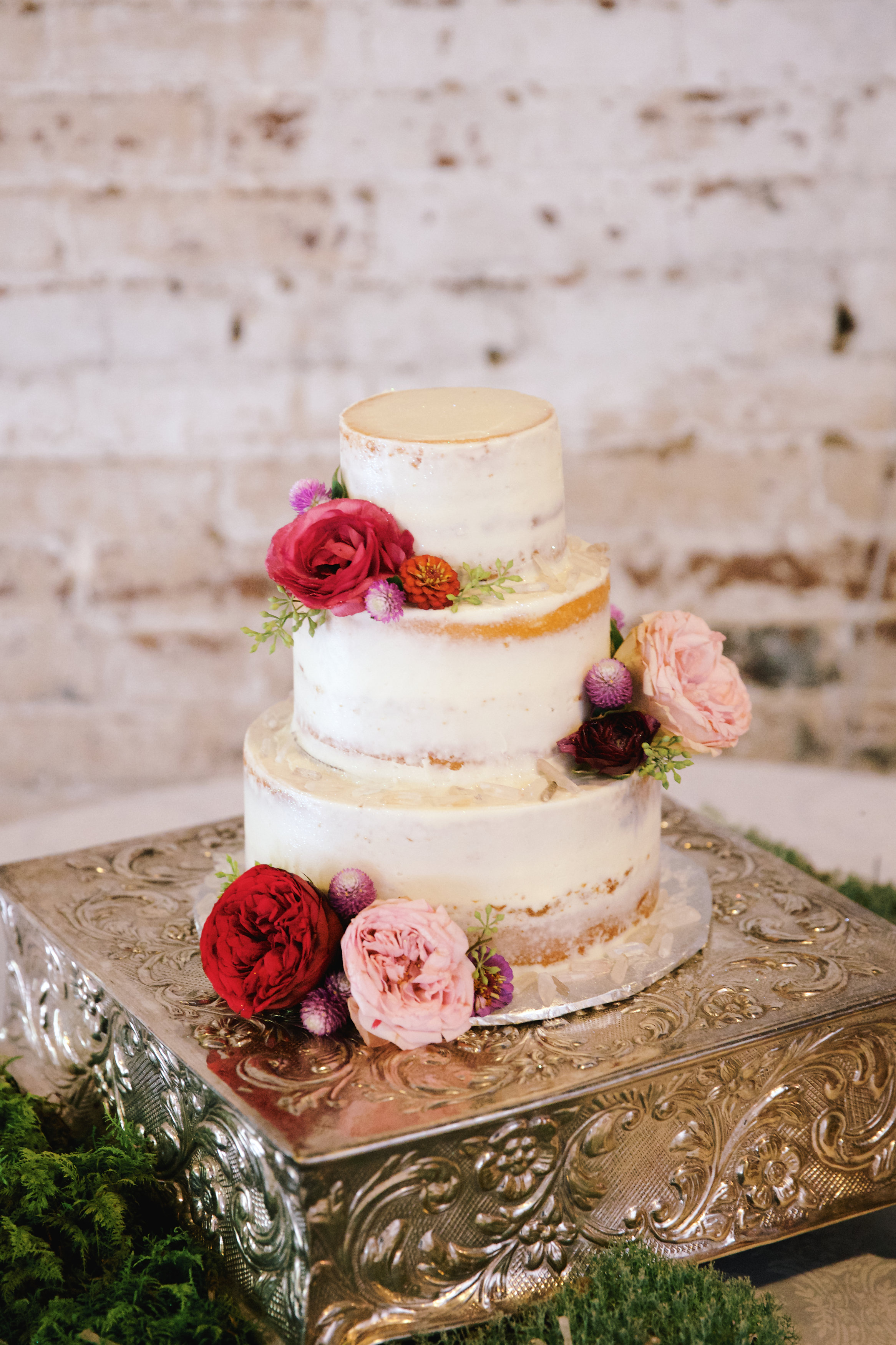 """A current wedding trend, the """"unfinished"""" bare theme is popular among brides today. Instead of several layers of buttercream or fondant, cake designers are leaving parts of the cake exposed, for a fresh, creative look.  Photo:  Olivia Rae James"""