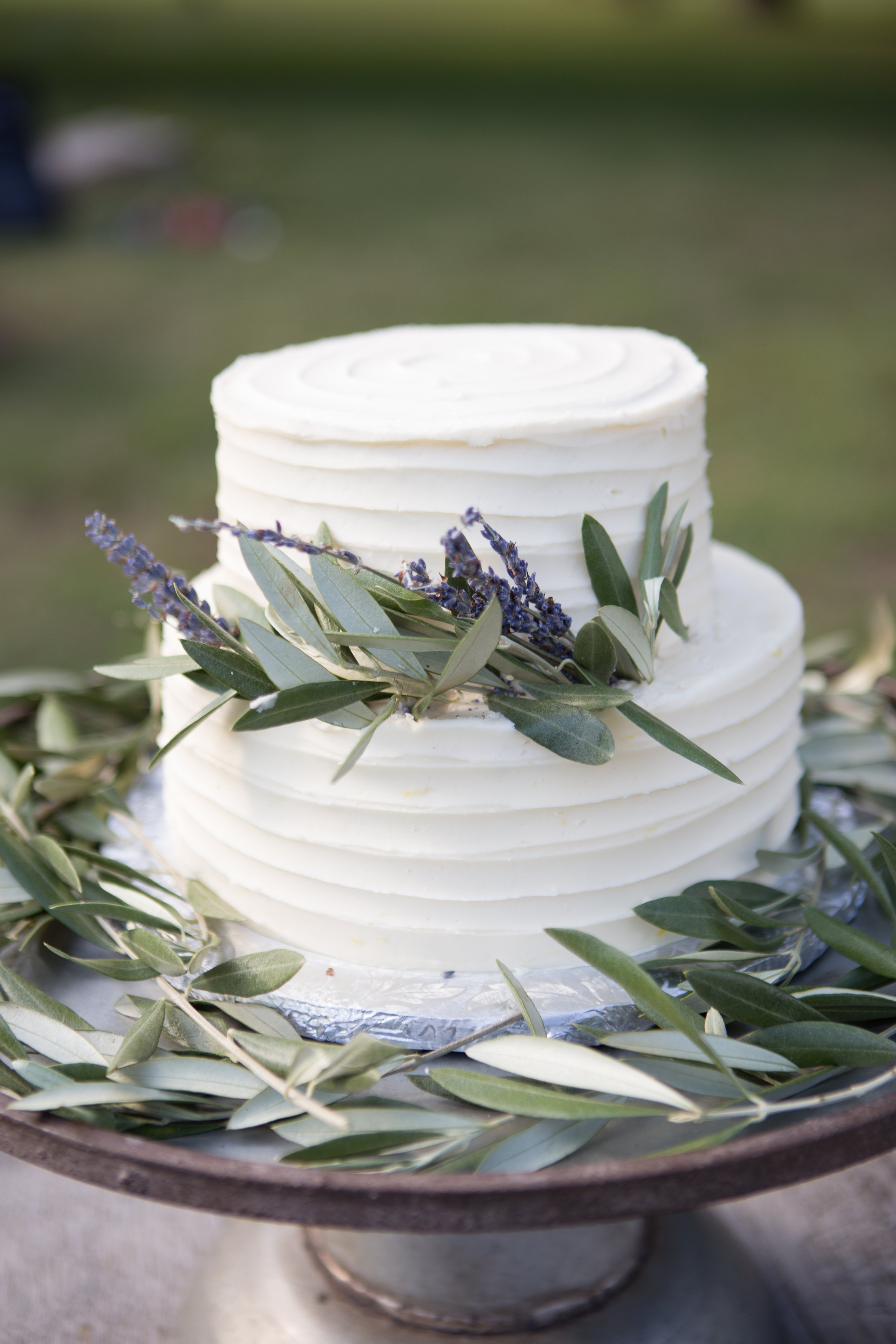 A simple textured three-tiered confection wrapped in sprigs of lavender and greenery perfectly compliments a rustic, earthy, or woodland-inspired celebration.   Photo: Smith Studios Photography