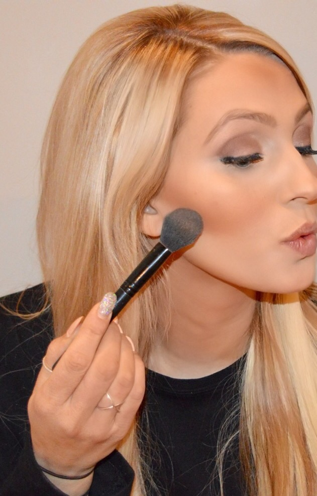 making a kissing face, I apply my bronzer by Mac in 'give me sun' in the hollow of my cheek.