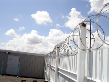 Solid Steel Fencing and Razor Wire.JPG