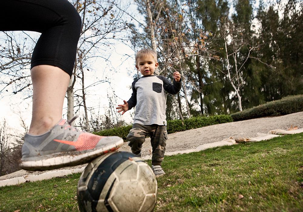Ryan and mom kick the soccer ball around.