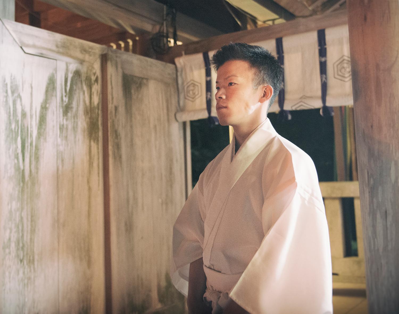 The night before the Aofushigaki Ritual at Miho Shrine. A Kannushi (Shinto priest) watches the preparation of the ritual.
