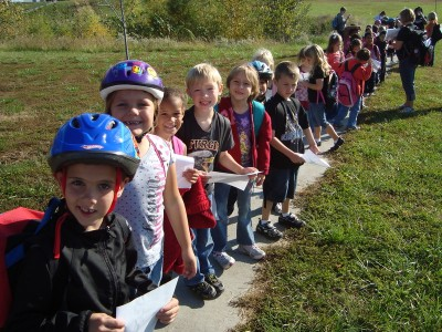 Bike49 Day: the first graders head out on a walk, wearing bike helmets because bike49 does.