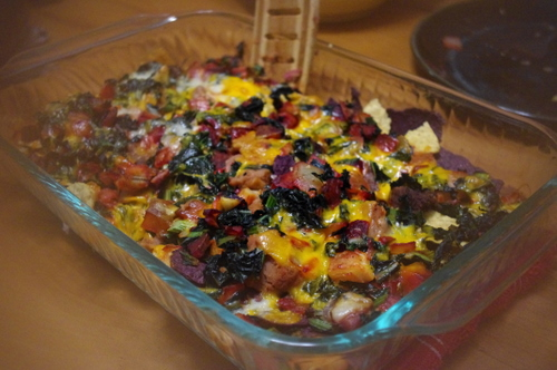 There are nachos buried beneath the cheese and veggies. On top are beets and kale.
