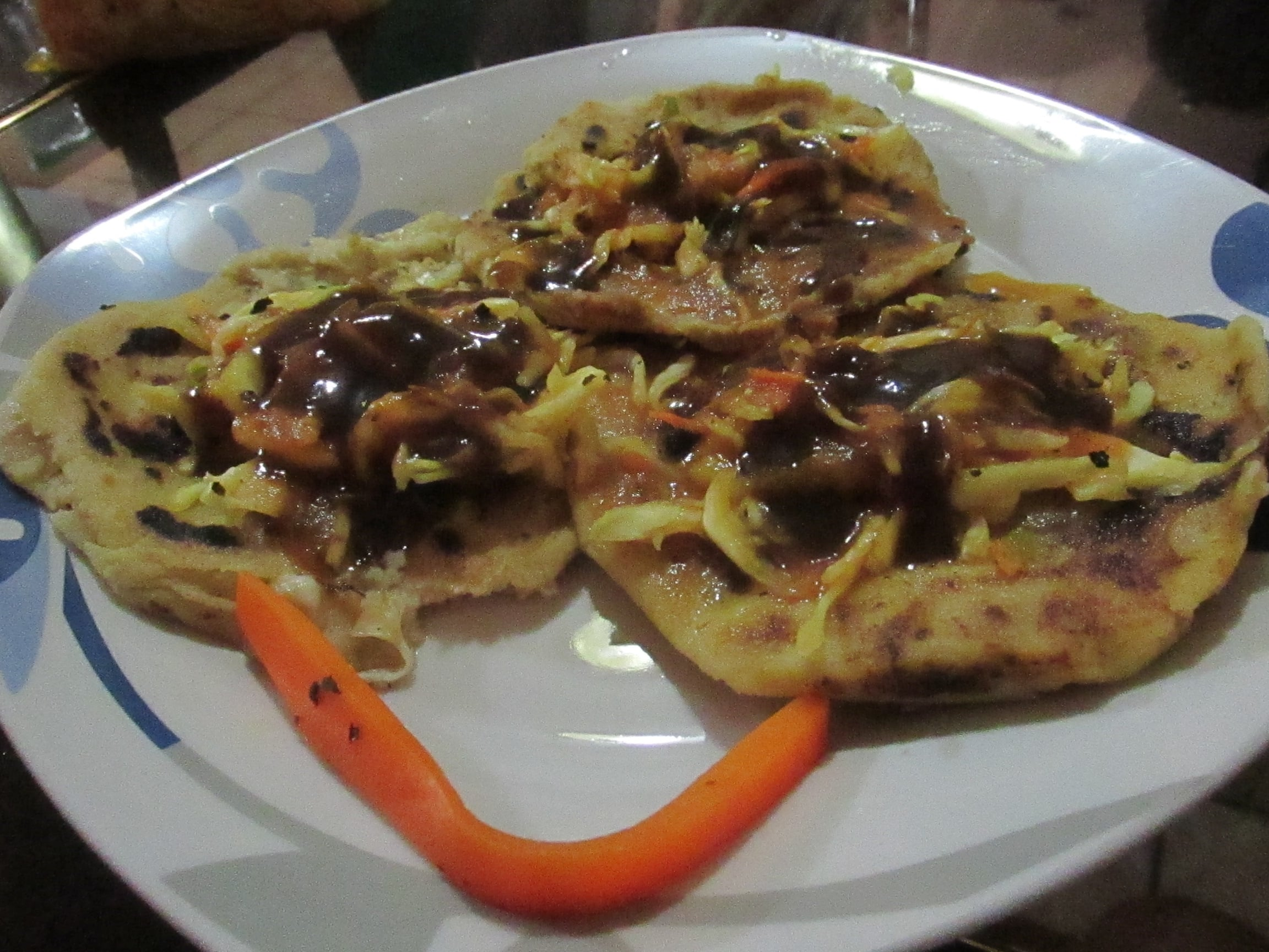 Several pupusas decorated with spicy vegetables and salad.