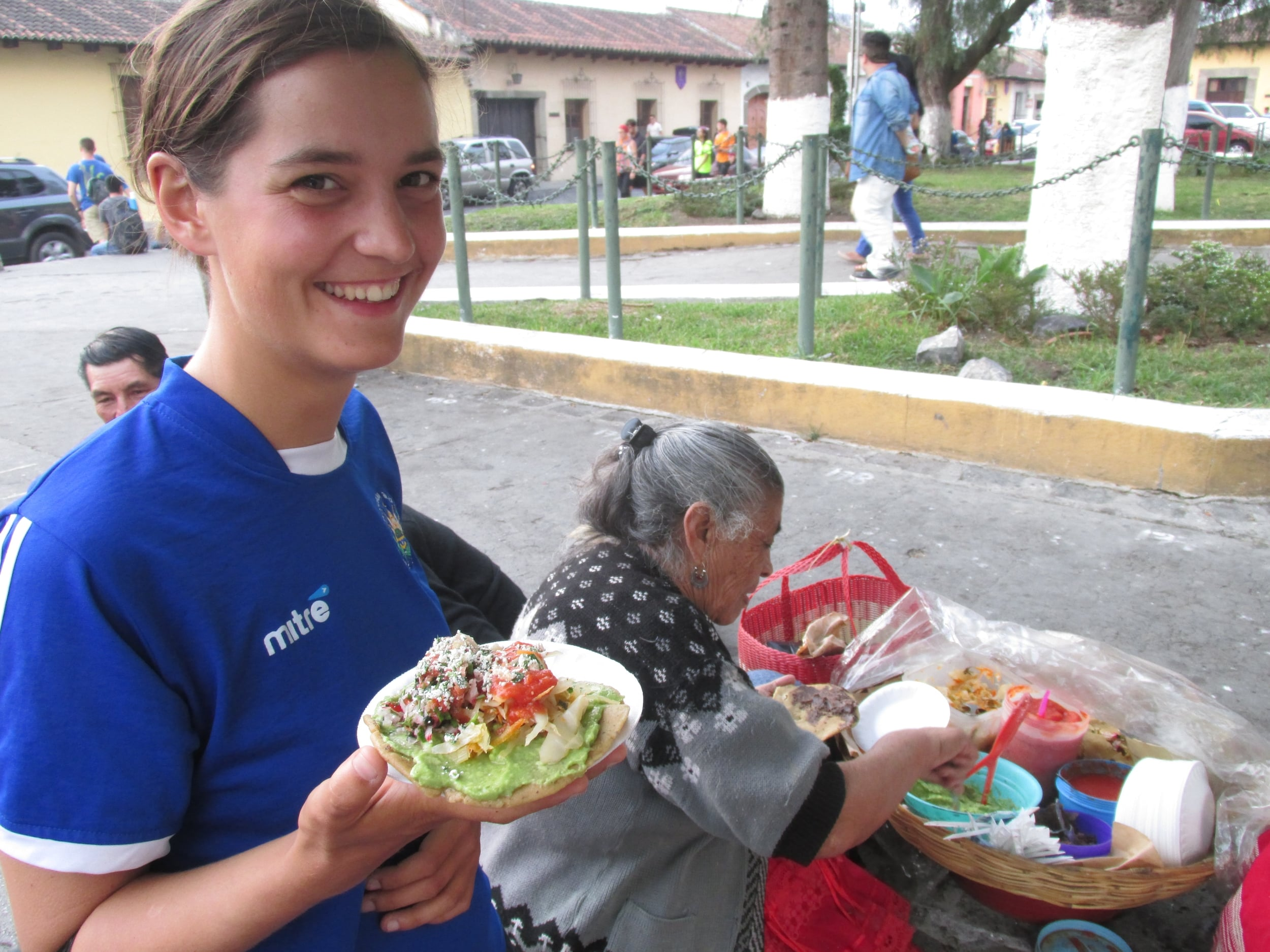 Nia eating a fried tortilla topped with BEANS and guacamole.