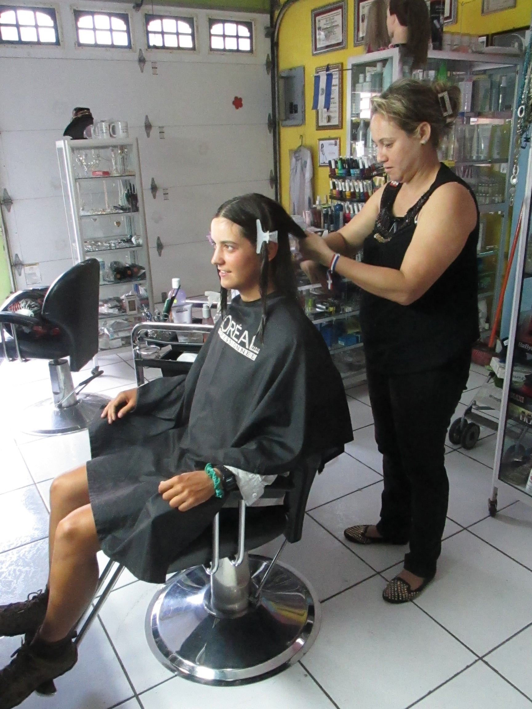 Lorena cuts Nia's hair in her hair salon at the front of her house.