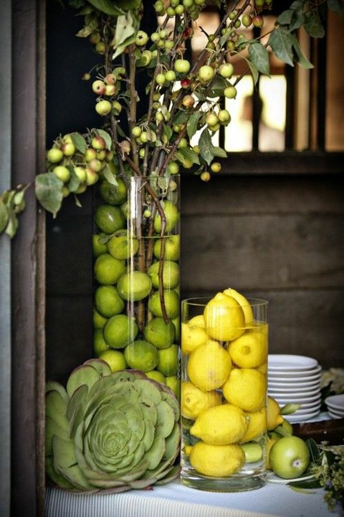 4.  FRUITFUL CENTERPIECES BY CONFRARIA DAS TRUFAS: Create a fresh, brightly colored table withlemons and limes in water filled  cylinder vases .