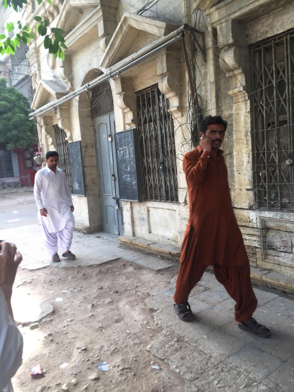 Two men walking on the side-walk in the inner city of Old Town, Karachi | Copyright Marvi Mazhar & Associates