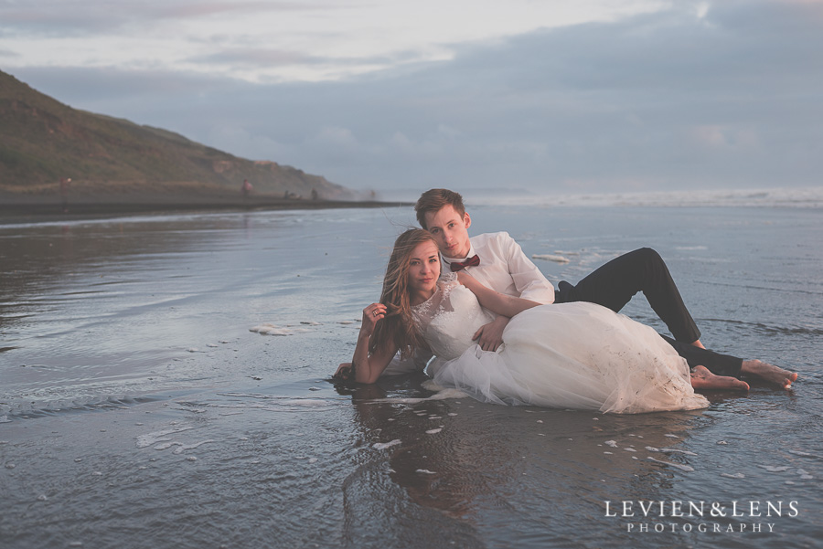 Bride and groom laying on the black sand