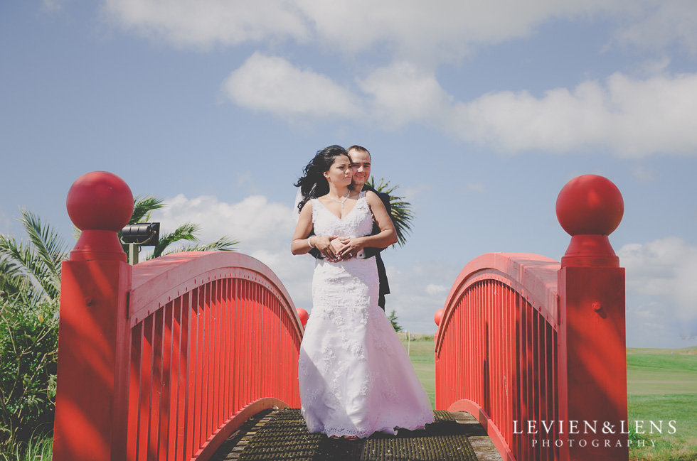 bride-groom hug on red bridge Formosa Golf Resort {Auckland wedding-engagement-couples photographer}