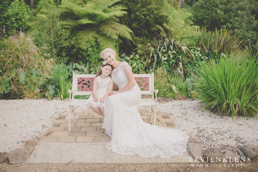 flower girl and stunning bride on bench {Auckland-Hamilton wedding photographer} Footbridge Lodge