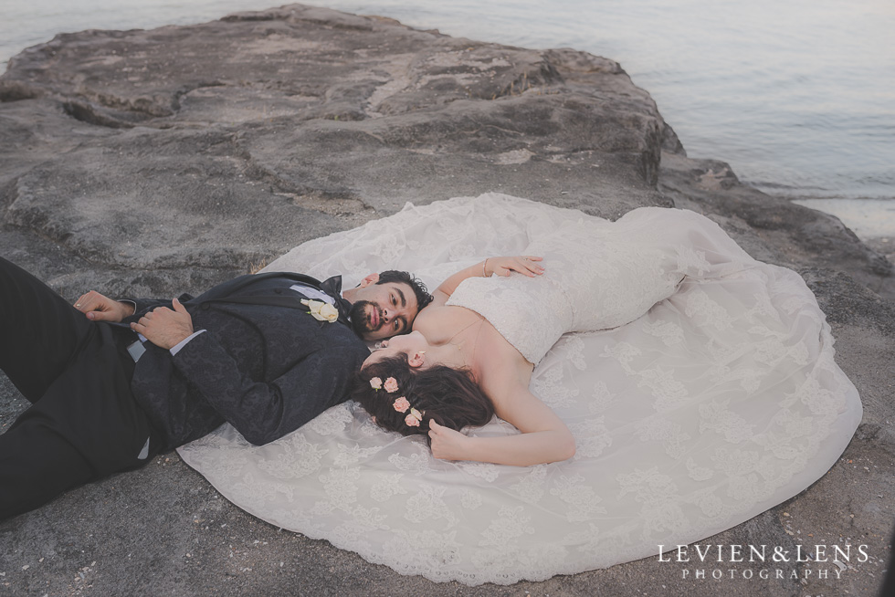 stunning bride and groom laying on rock St Heliers beach {Auckland-Hamilton-Tauranga wedding photographer}