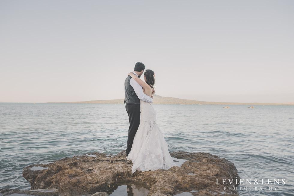 bride and groom look at ocean back St Heliers beach {Auckland-Hamilton-Tauranga wedding photographer}