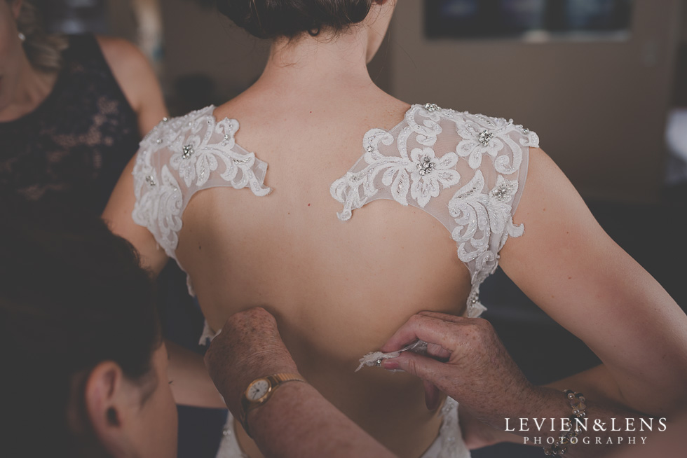 bride getting ready putting dress on Castaways Resort - Kariotahi beach wedding {Auckland lifestyle couples-engagement photographer}