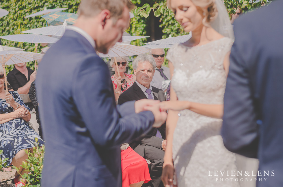 groom putting ring on bride hand {Tauranga-Bay of Plenty wedding-couples-engagement photographer}