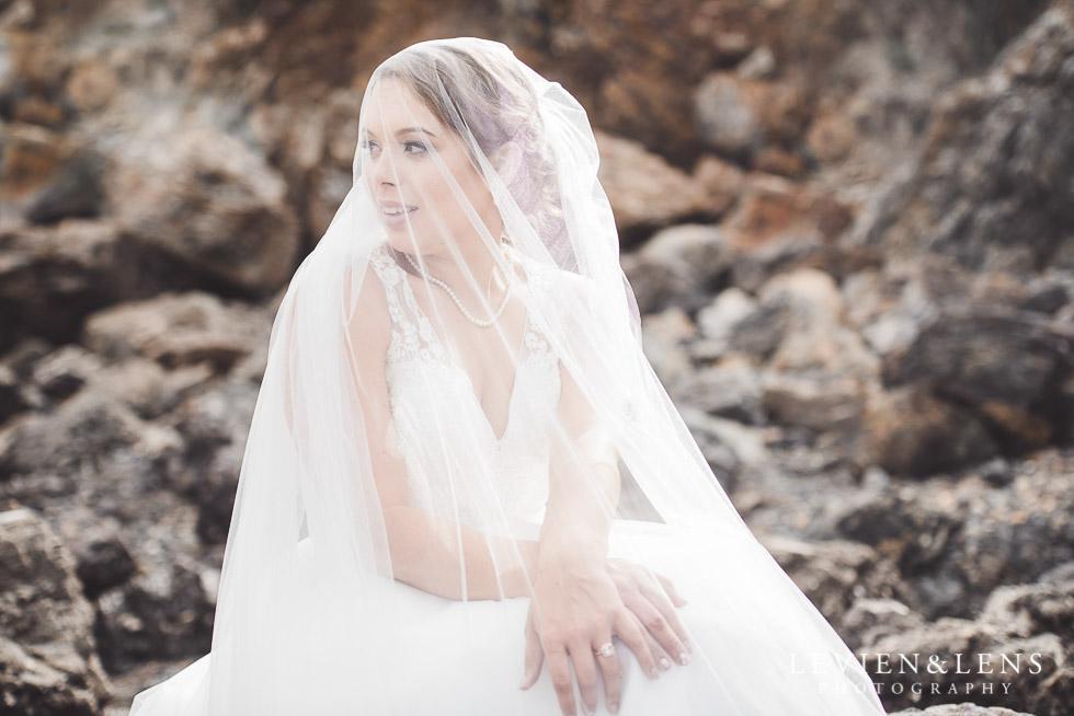 bridal portraiture - bride under veil sitting on rocks - The Duke of Marlborough Hotel - Russel wedding {Northland-New Zealand weddings photographer} beach