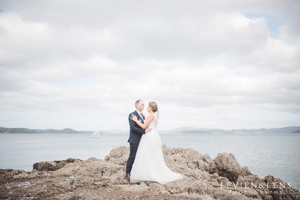 bride groom on rocks - edge - The Duke of Marlborough Hotel - Russel wedding {Northland-New Zealand weddings photographer} beach
