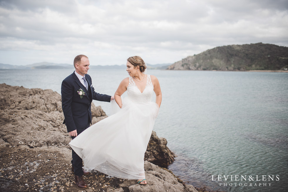 bride walking on rocks cliff - The Duke of Marlborough Hotel - Russel wedding {Northland-New Zealand weddings photographer} beach