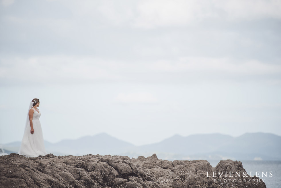 bride standing on rocks - The Duke of Marlborough Hotel - Russel wedding {Northland-New Zealand weddings photographer} Long Beach