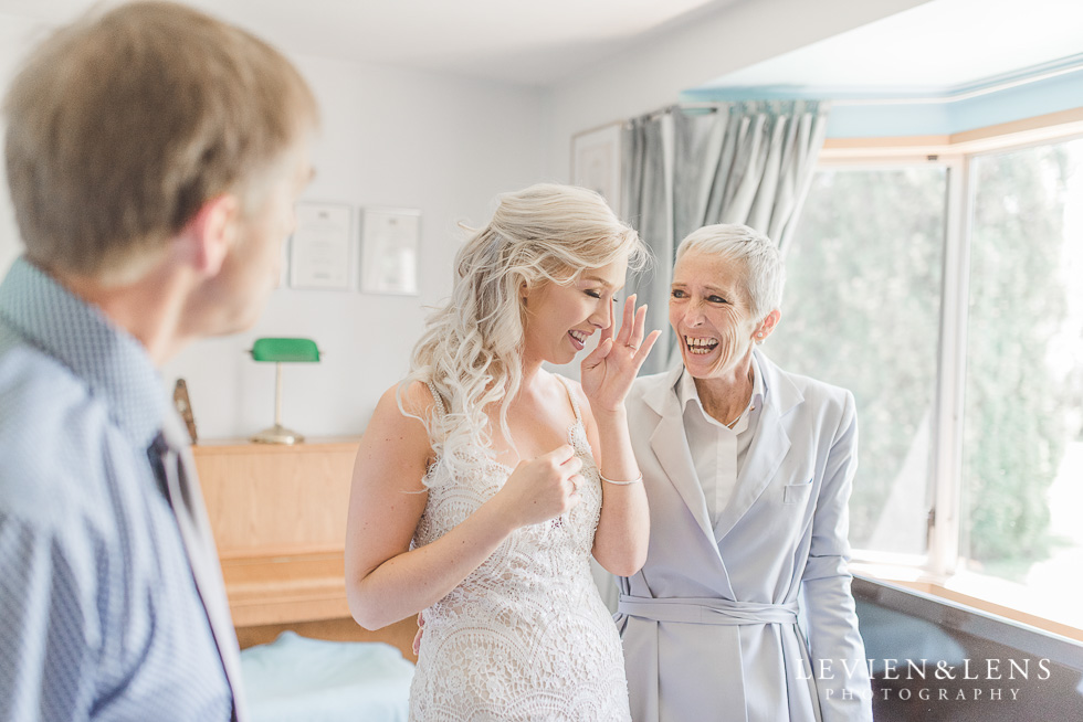 bride crying at getting ready surrounded by parents